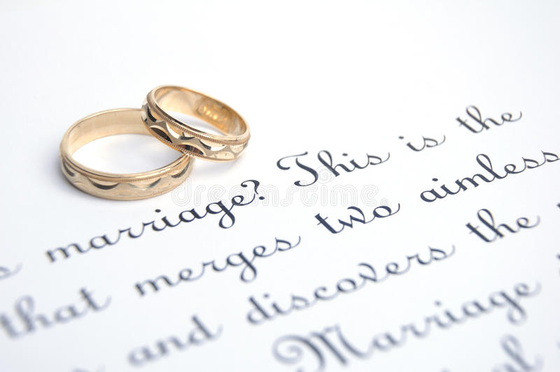 Wedding golden rings and vow. Two wedding golden rings on a paper with text of wedding vow stock photo