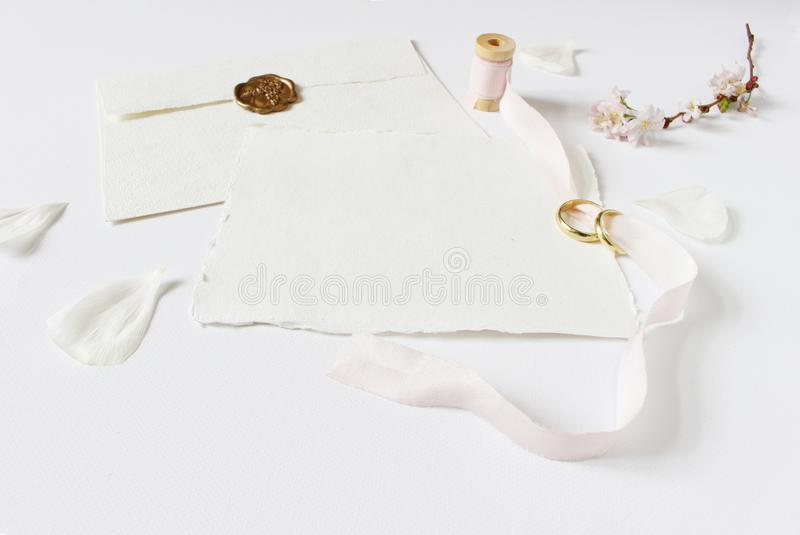 Wedding greeting card, invitation with two golden rings, cherry tree blossoms, white rose petals, spool of pink silk. Ribbon and handmade envelope with a seal royalty free stock image