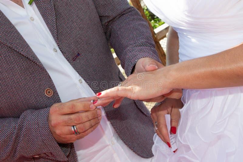 Wedding groom wears bride ring exchange royalty free stock photography