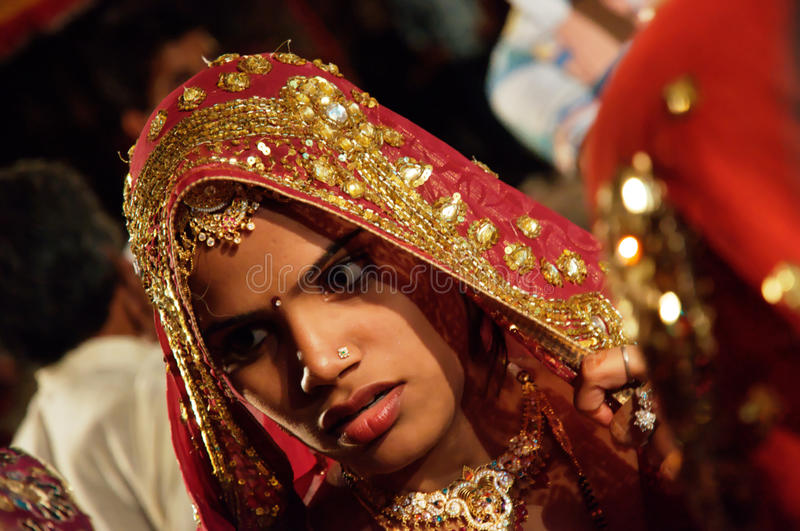 Wedding guest. A beautiful young girl wearing a traditional long scarf or pashmina stole to cover her head during a wedding ceremony in India. Jewelry is a key
