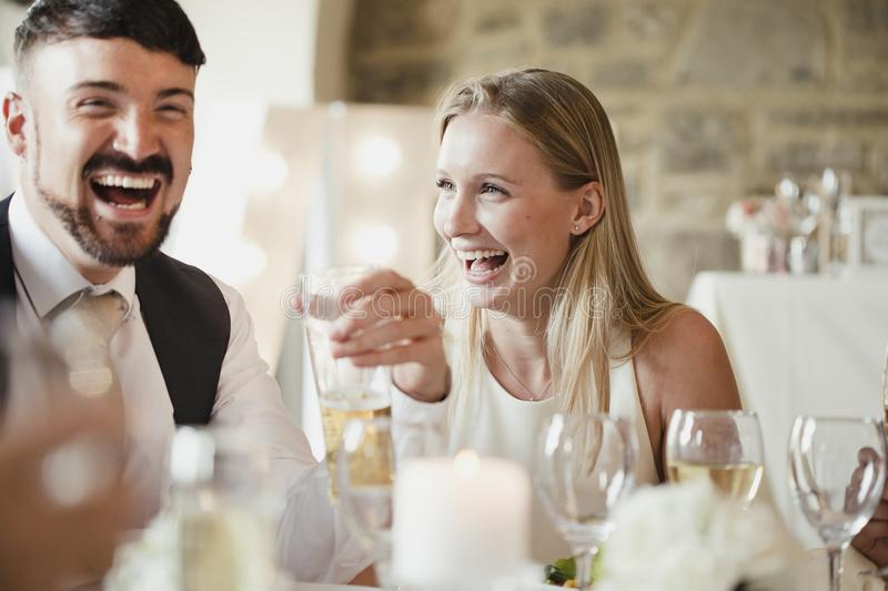 Wedding Guests At The Dinner Party. Wedding guests are enjoying themselves while sitting at the table for the meal. They are talking and laughing while drinking stock photo