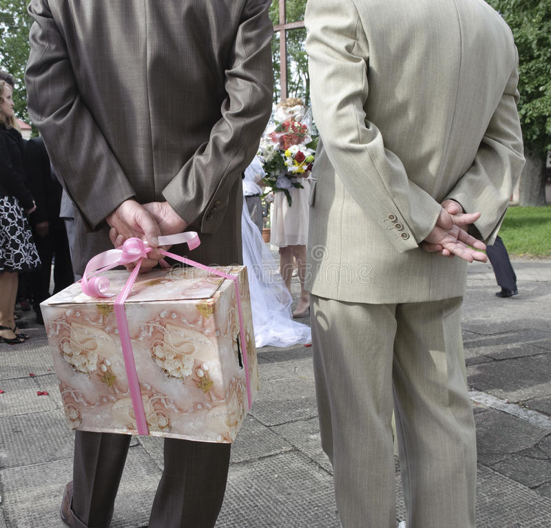 Wedding guests holding gift. Rear view of two wedding guests, one holding large present behind back stock photos