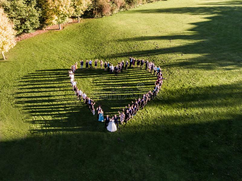 Wedding guests lined up in the shape of heart with bride and groom marriage people. Wedding guests lined up in the shape of heart with bride and groom. marriage royalty free stock photography