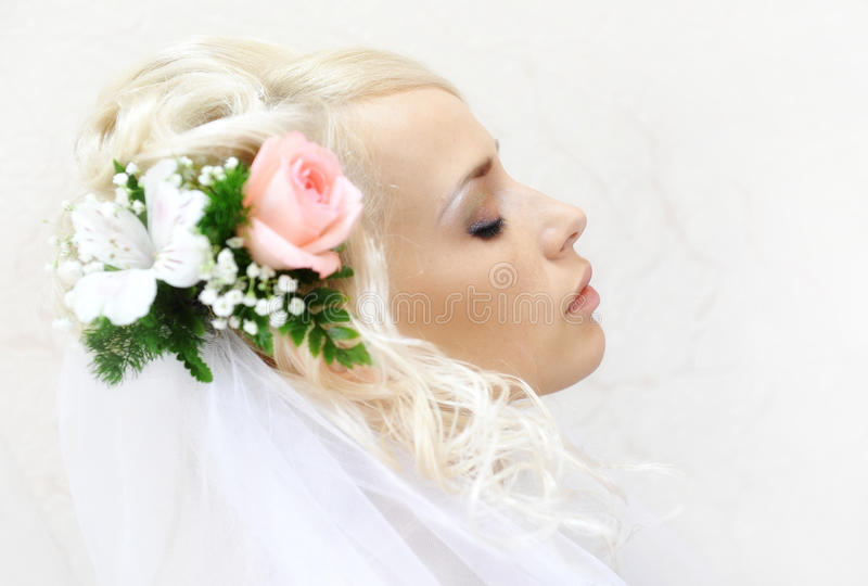 Wedding hairstyle with flowers. Beautiful bride with wedding hairstyle side view stock images