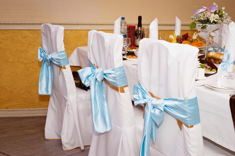 Wedding hall decoration. Chairs in a case with blue ribbons. Wedding hall decoration. Chairs in a white case with blue ribbons royalty free stock image
