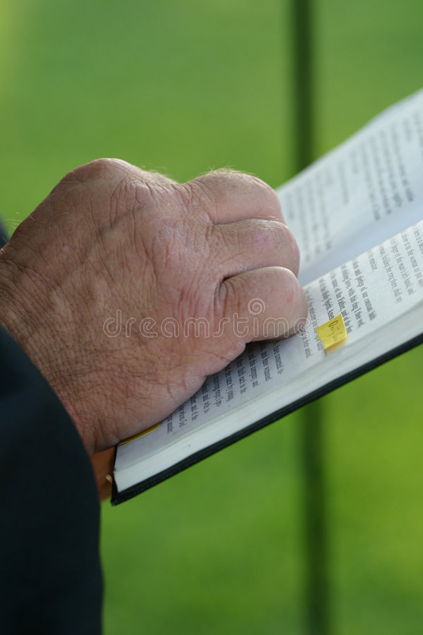 Wedding Hand on Bible. This was from a wedding ceremony. It is a close up of the priest's hand on the Bible as he read scripture. Can obviously be used royalty free stock photos