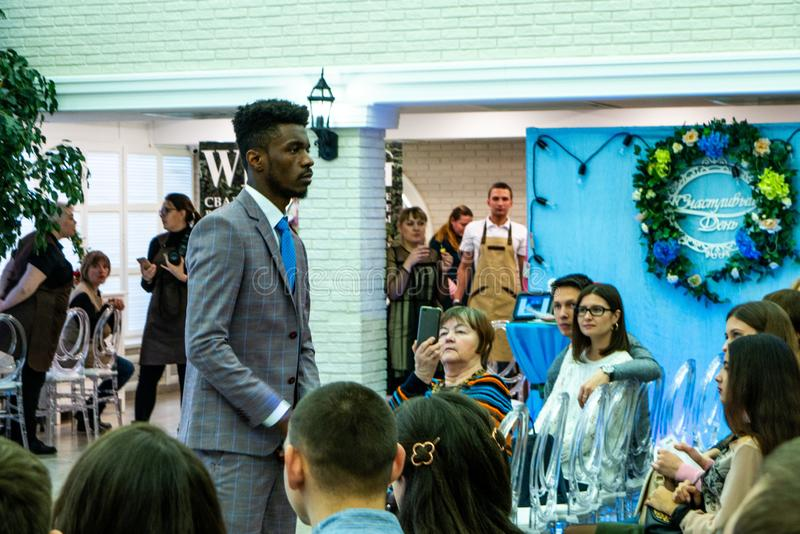 An afro-american groom model in a wedding suit. At the exhibition Wedding hassle 2019 took place in Kirov, Russia stock photos