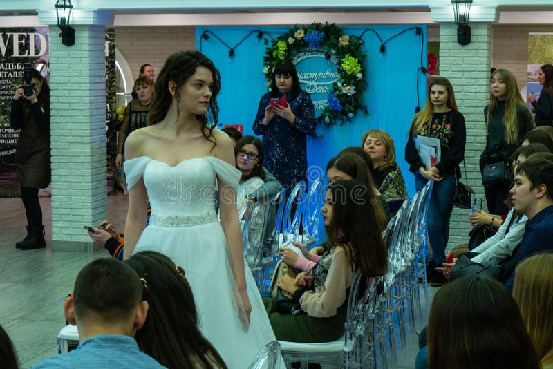 A bride model in a white wedding dress staying among guests. At the exhibition Wedding hassle 2019 took place in Kirov, Russia stock photography