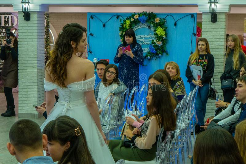A bride model in a white wedding dress among guests. At the exhibition Wedding hassle 2019 took place in Kirov, Russia royalty free stock photography