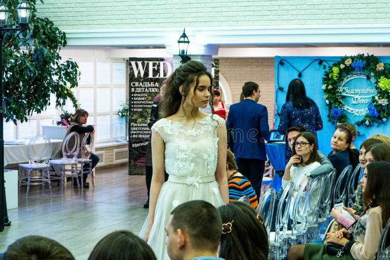 A bride model demonstrates a white wedding dress to guests. At the exhibition Wedding hassle 2019 took place in Kirov, Russia stock image