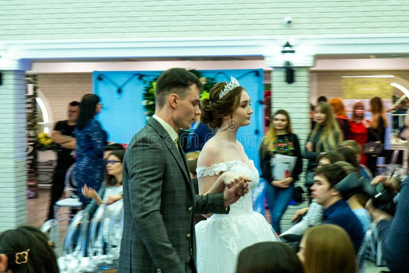A groom and a bride models in wedding clothes passing the guests. At the exhibition Wedding hassle 2019 took place in Kirov, Russia stock photo