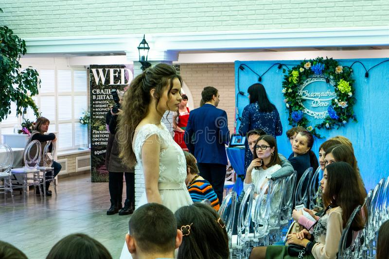 A bride model demonstrates a beautiful white wedding dress to the guests. At the exhibition Wedding hassle 2019 took place in Kirov, Russia stock photography