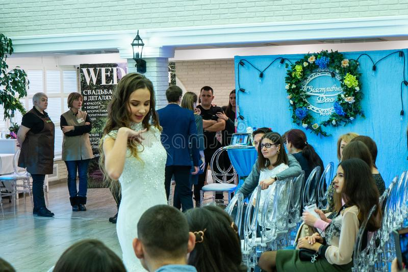 A bride model in a specific pose demonstrates a white wedding dress. At the exhibition Wedding hassle 2019 took place in Kirov, Russia royalty free stock photos