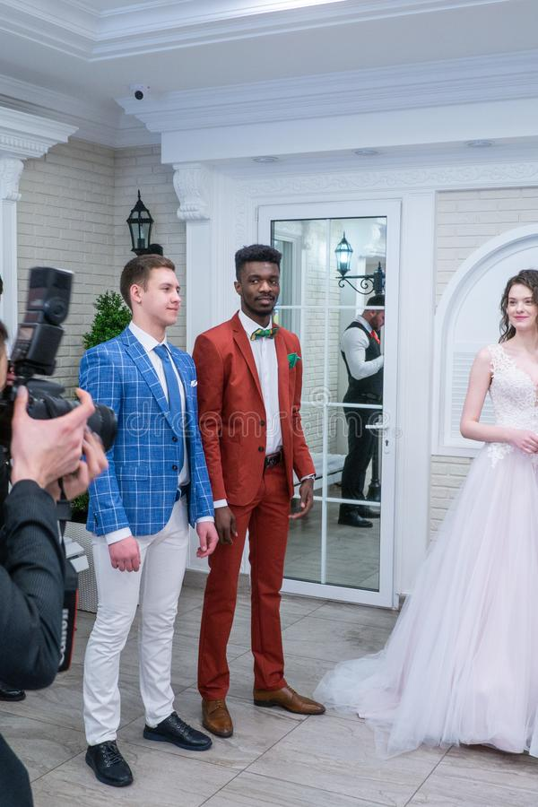 A pair of groom models posing for the camera in wedding suits. At the Wedding hassle 2019 exhibition took place in Kirov, Russia stock photography