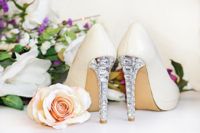 The heels of wedding shoes are decorated with precious stones. Wedding high-heeled shoes stand on a white dresser against a background of beautiful flowers royalty free stock image