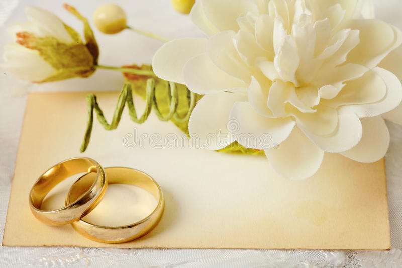 Wedding invitation. Wedding background with two gold wedding rings, flowers and empty card stock photos