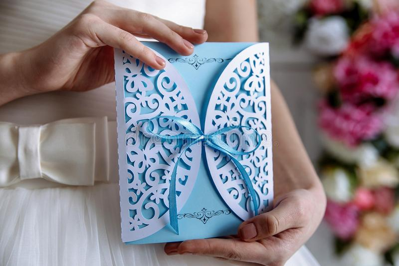 Wedding invitation blue card in hands. Wedding invitation blue card in the hands of the bride stock photo