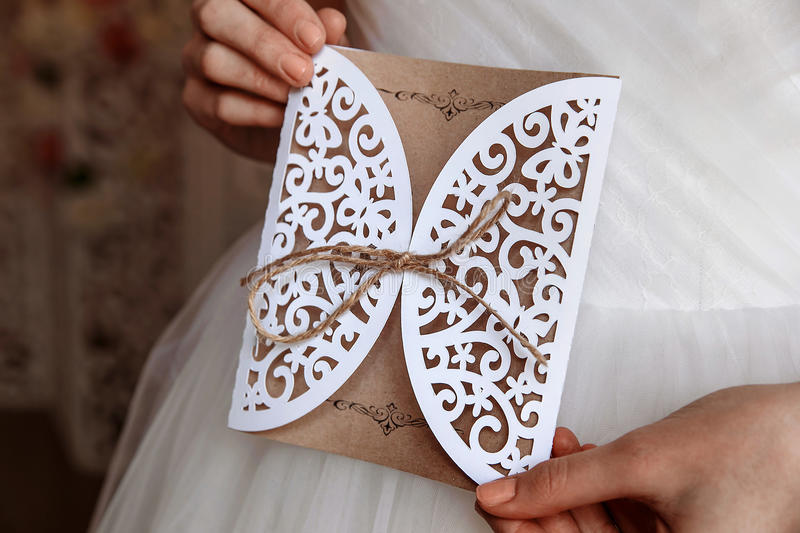 Wedding invitation card in hands. In rustic style royalty free stock photo