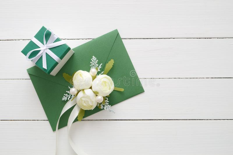 Wedding invitation card or Valentines Day letter in green envelope decorated with white rose flowers and gift box. Flat lay. Top view. Copy space for text royalty free stock photos