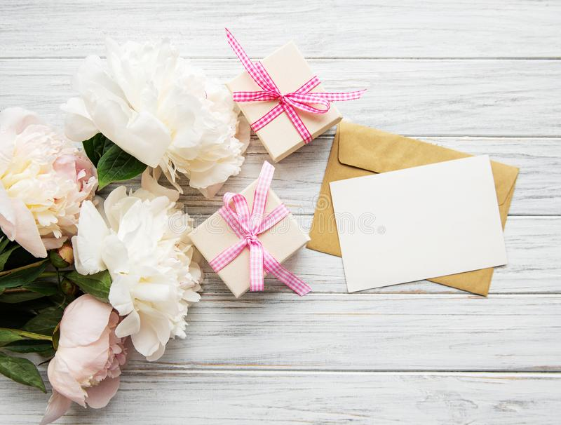 Envelope with pink peonies. Wedding invitation and envelope with pink peonies on a old white wooden background royalty free stock images