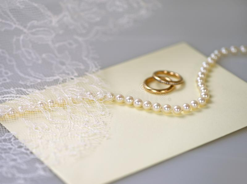 Wedding invitation with a pearl necklace and golden rings. Wedding invitation with a pearl necklace, two golden rings and white lace stock image