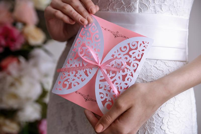 Wedding invitation pink card In the hands of the bride. Wedding invitation pink card in hands stock photography