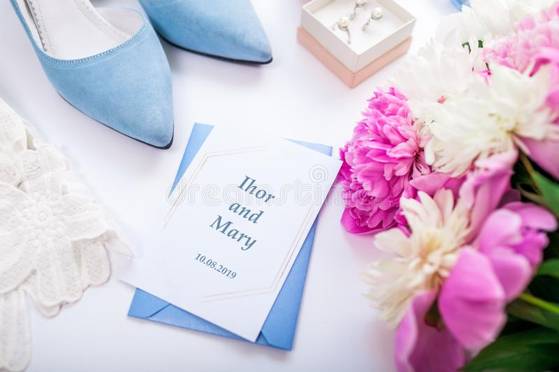 Wedding invitation surrounded with flowers, bride`s shoes and jewellery. Morning of bride stock photos