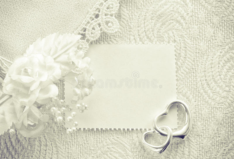 Wedding invitation, valentine day concept, monochrome card. With a clothes detail lace, boutonniere, two silver heart pendant stock image