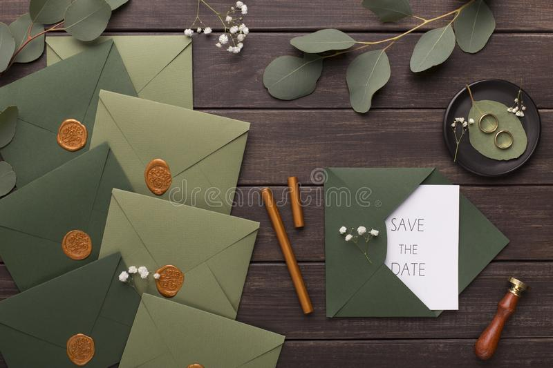 Wedding invitations save the date in green envelopes. On wooden table royalty free stock photo