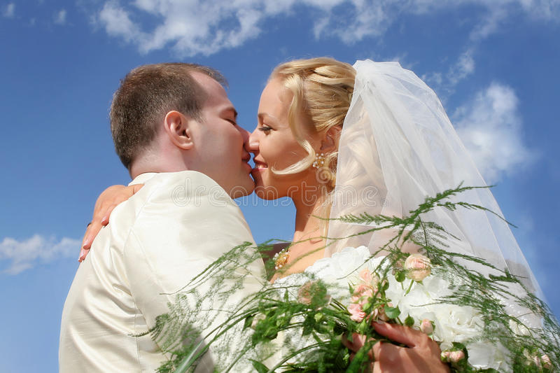 Wedding kiss. Wedding couple kissing on blue sky background stock photography