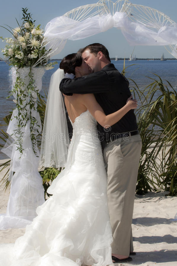 Wedding kiss. A couple kissing under arch during beach wedding ceremony stock photo