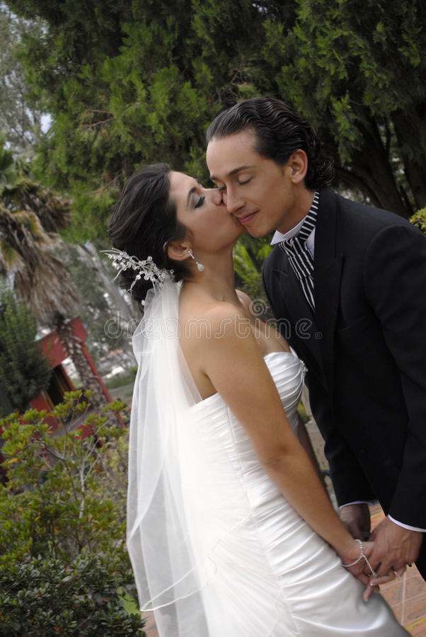 Wedding kiss. Happy wedding couple, shes kissing him stock image
