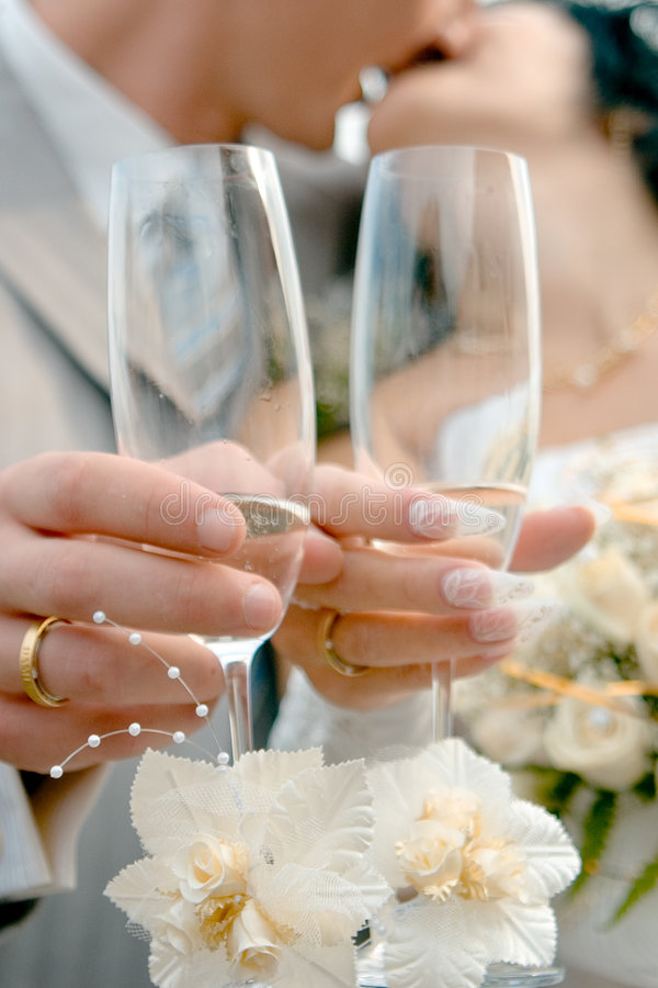Wedding kiss. Wedding glasses with champagne over kissing bride and groom