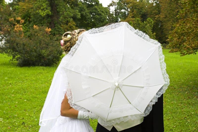 Wedding kiss behind umbrella royalty free stock photos