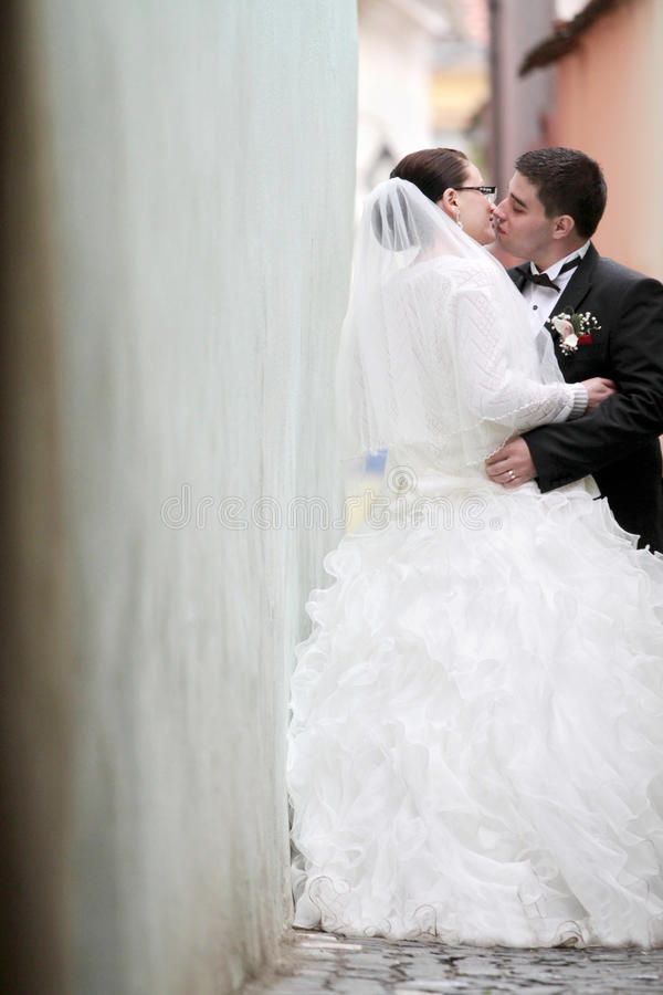Wedding kiss. Embraced wedding couple kiss outdoors royalty free stock images