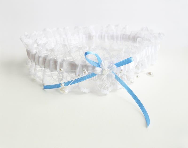 Wedding lace garter. White wedding lace garter with blue ribbon royalty free stock photos
