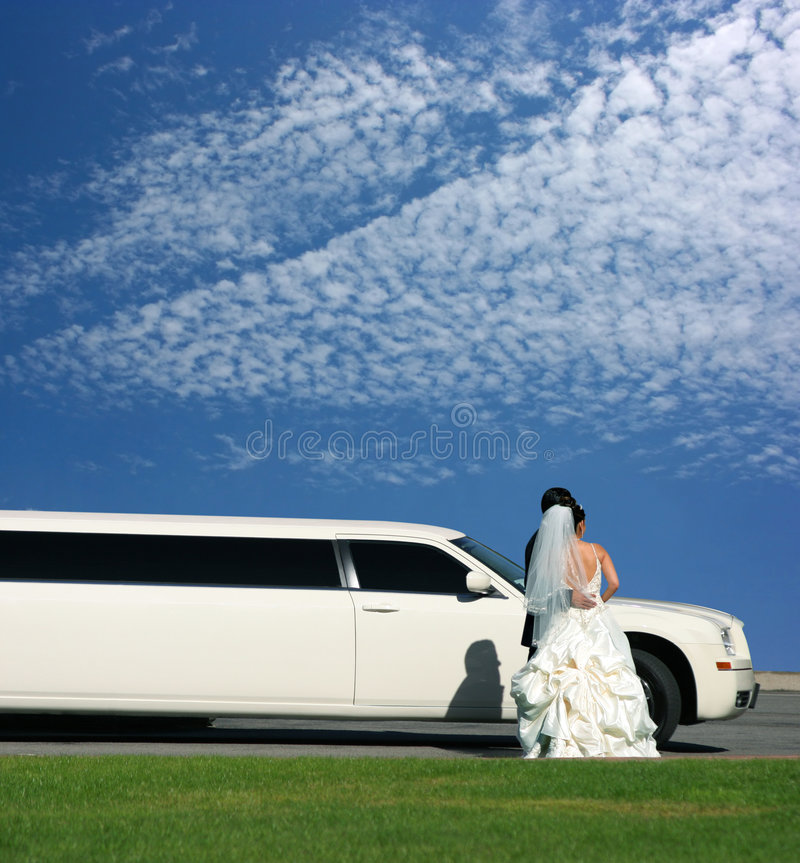 Wedding and limousine. Groom and bride on wedding day next to the limousine stock image