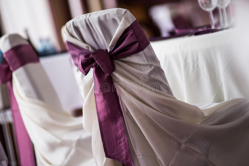 Wedding location. White chair with purple ribbon decoration stock image