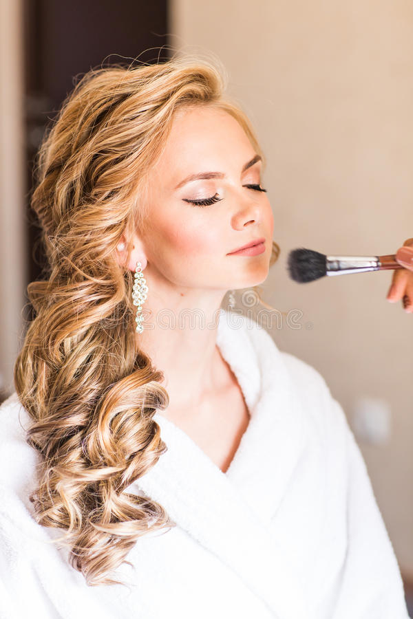 Wedding makeup artist making a make up for bride. Beautiful model girl indoors. Beauty blonde woman with curly hair. Female portrait. Bridal morning of a cute stock photo