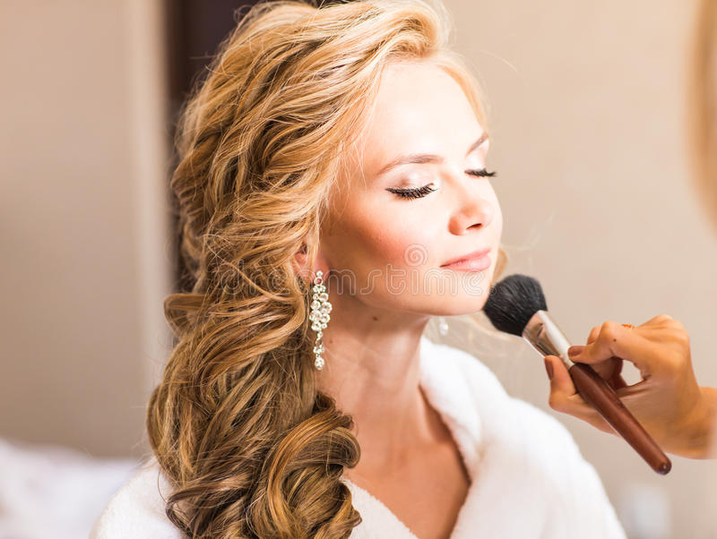 Wedding makeup artist making a make up for bride. Beautiful model girl indoors. Beauty blonde woman with curly hair stock photo