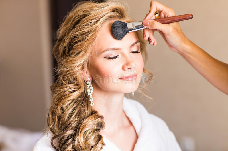 Wedding makeup artist making a make up for bride. Beautiful model girl indoors. Beauty blonde woman with curly hair. Female portrait. Bridal morning of a cute stock image