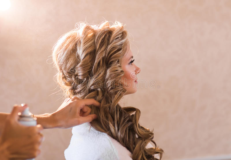 Wedding makeup artist making a make up for bride. Beautiful model girl indoors. Beauty blonde woman with curly hair. Female portrait. Bridal morning of a cute royalty free stock photography