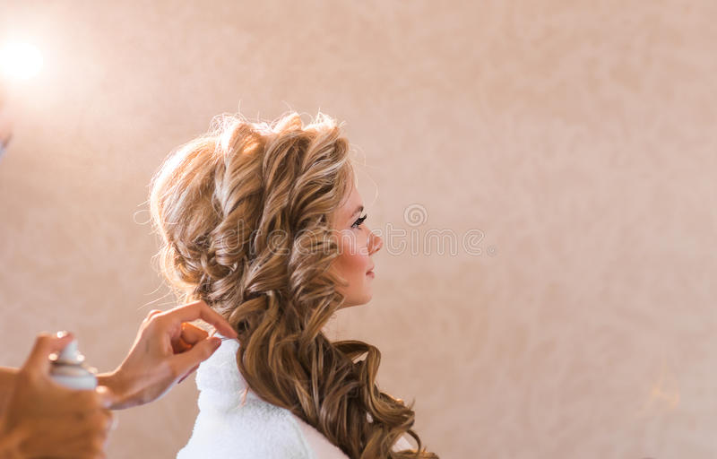 Wedding makeup artist making a make up for bride. Beautiful model girl indoors. Beauty blonde woman with curly hair. Female portrait. Bridal morning of a cute royalty free stock photos