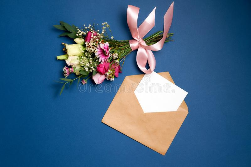 Wedding Marriage or Valentines Day composition. Bunch of flowers kraft paper envelope with blank white letter with copy space lay on blue background. Mother`s stock image