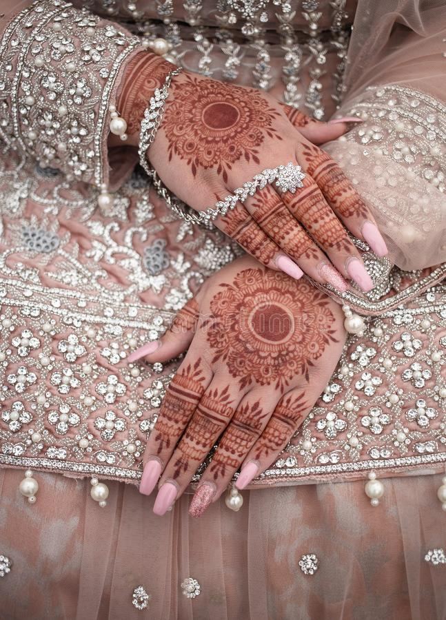 Wedding Mehndi on bride`s hands. Mehndi is a form of body art originating from the Arabian peninsula, in which decorative designs are created on a person`s body stock image