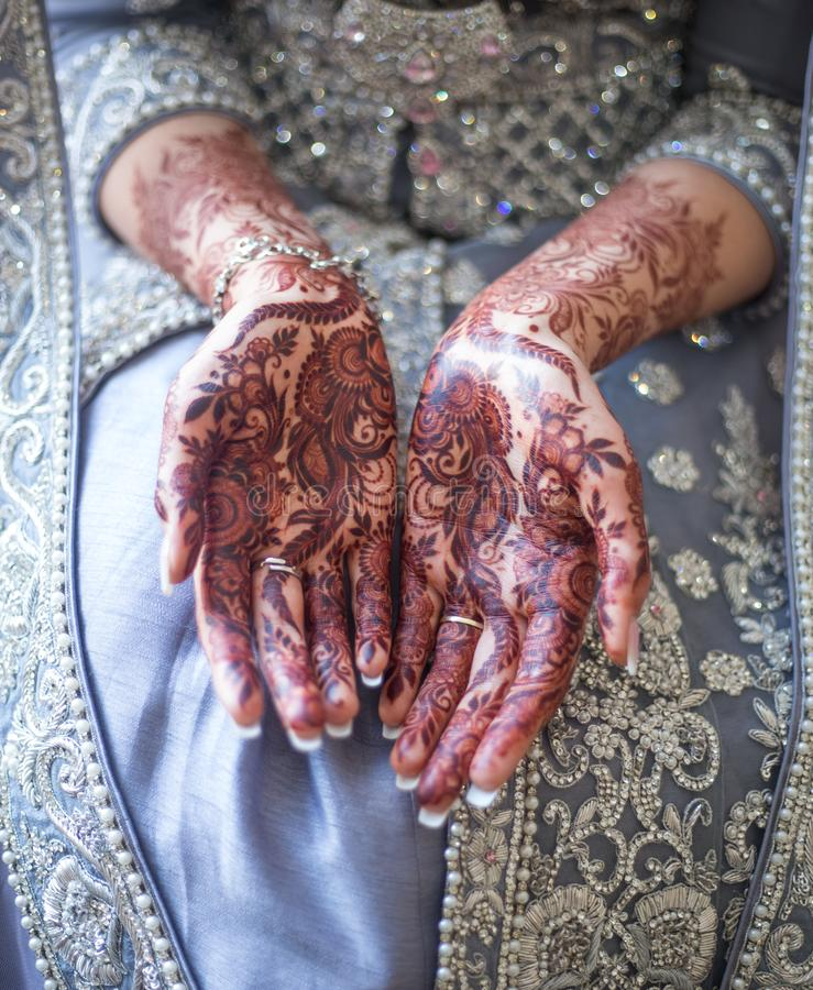 Wedding Mehndi on bride`s hands. Mehndi is a form of body art originating from the Arabian peninsula, in which decorative designs are created on a person`s body stock images