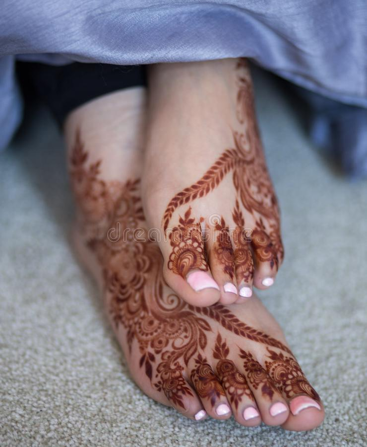Wedding Mehndi on bride`s legs. Mehndi is a form of body art originating from the Arabian peninsula, in which decorative designs are created on a person`s body stock image