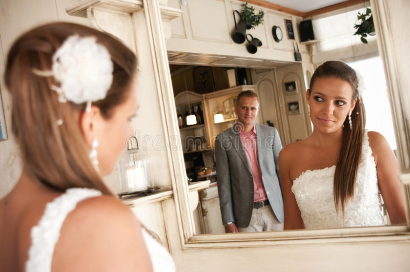 Wedding mirror couple. Creative wedding image of a bride looking at the groom in the mirror stock photography