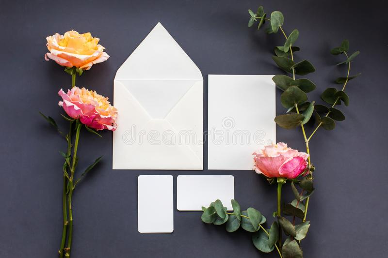 A wedding mock up composition. Wedding Invitation, envelope, paper cards with peony rose flower and sprig of eucalyptus stock image