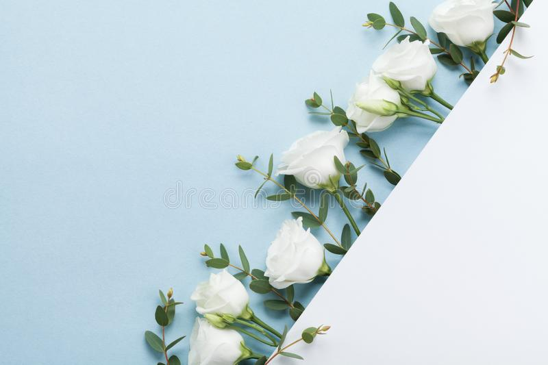 Wedding mockup of paper card decorated beautiful white flowers and green leaves on pastel background top view. Flat lay style. stock images